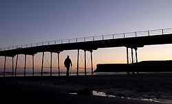 (c) Licensed to London News Pictures. 04/12/2015<br /> Saltburn. UK. <br /> A man walks on the beach towards Saltburn pier as the first light of day rises up over the cliffs of Huntcliff.<br /> Photo credit : Ian Forsyth/LNP