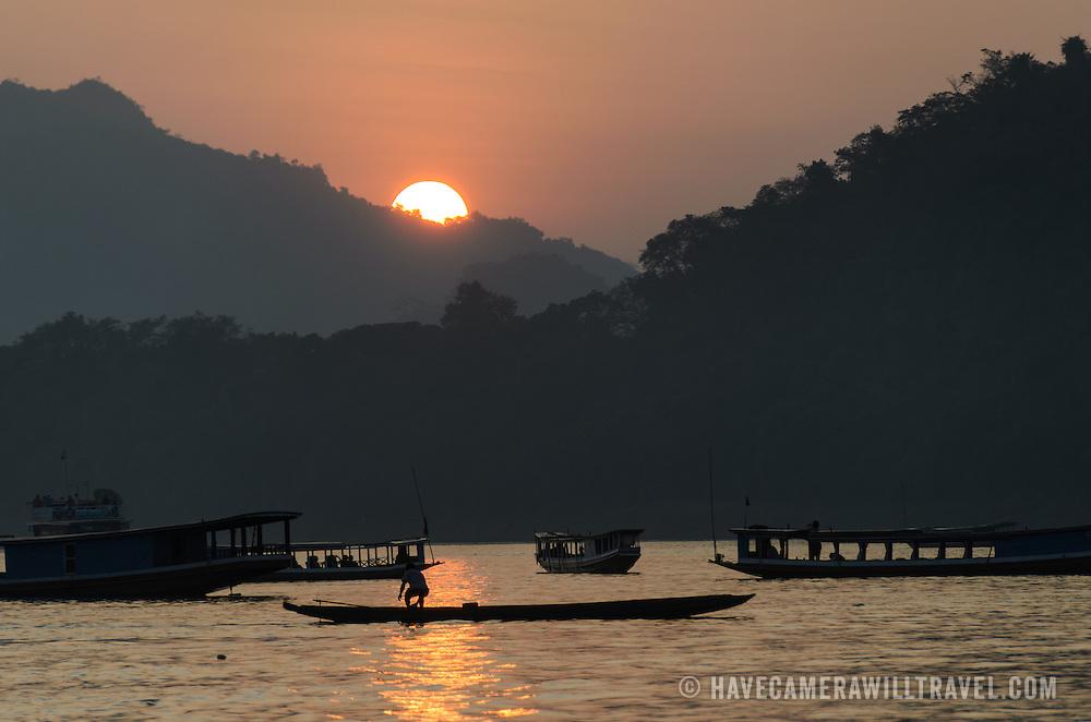 Boats on the river at sunset on the Mekong River near Luang Prabang, Laos.