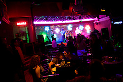 """People dance and drink and a nightclub while a group of Norteno musicians play music in downtown Culiacan.  Norteno music is famous for its """"corridos"""", or ballads.  Many musicians compose corridos about drug lords that become part of popular culture.  This style of music is increasingly popular and is part of Mexico's emerging Narco culture."""
