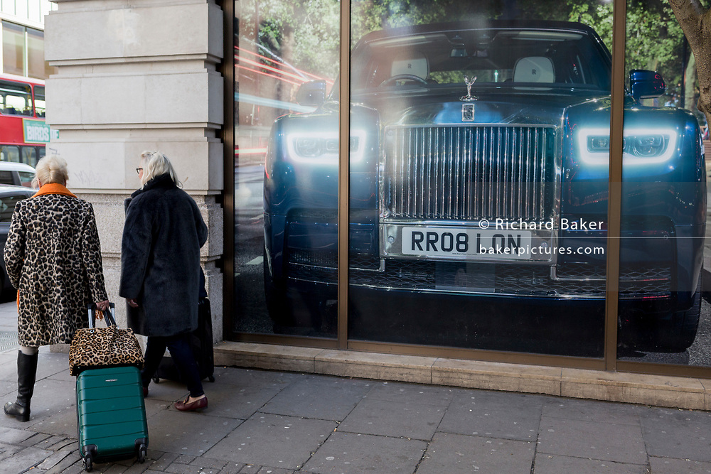 Two wealthy women, one wearing a Leopard  printed coat and pulling a bag behind her, walk past a large image of a Rolls-Royce, outside the car brand's Mayfair show room, on 18th February 2020, in London, England.