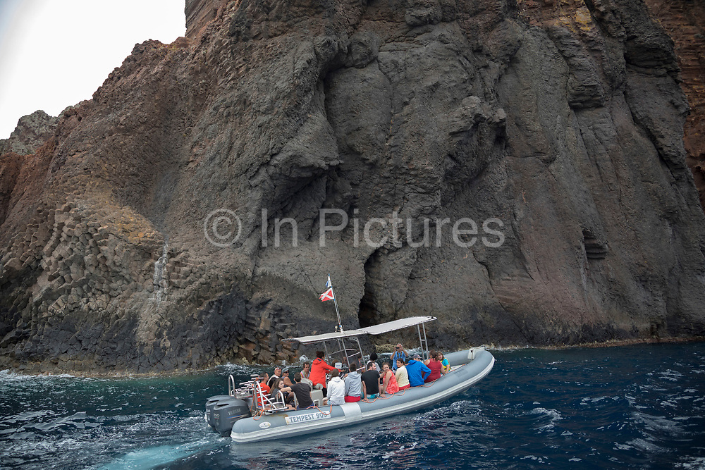 Tourist boat passes the volcanic coastal landscape of the Scandola Nature Reserve on 15th September 2017 in Corsica, France. The Scandola Nature Reserve is located on the west coast of the Corsica, within the Corsica Regional Park. The reserve was established in 1975 and has been recognized by the United Nations as a Natural World Heritage Site, and was inscribed on the World Heritage List in 1983.