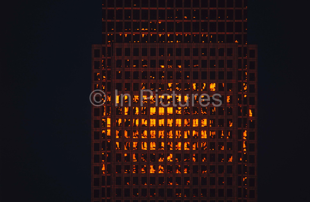 Canary Wharf tower seen through a telephoto lens from across West India Docks, London Docklands, East London England. We see dozens of office windows illuminated by fragmented solar light from a rising sun. Office windows reflect that golden orange light which underexposes the darkened sky behind and the remainder of the building. Canary Wharf is the product of the 1980s  financial boom when during the office of Prime Minister Margaret Thatcher, huge building projects such as the Docklands consortium saw vast changes in London's landscape.