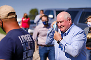 03 SEPTEMBER 2020 - RADCLIFFE, IOWA: SONNY PERDUE, the US Secretary of Agriculture takes off his face mask as he arrives on a farm in central Iowa. Perdue made a secretarial disaster declaration for 42 counties in central Iowa during a farm visit in central Iowa Thursday. Perdue was accompanied by Governor Kim Reynolds and US Senator Joni Ernst. The secretarial disaster declaration frees up more federal funds, from the Department of Agriculture, to help in recovery from the derecho storm that wiped out about one-third of Iowa's corn crop on Monday, August 10, 2020. Many Iowa farmers are still rebuilding lost buildings or plowing under lost crops.       PHOTO BY JACK KURTZ