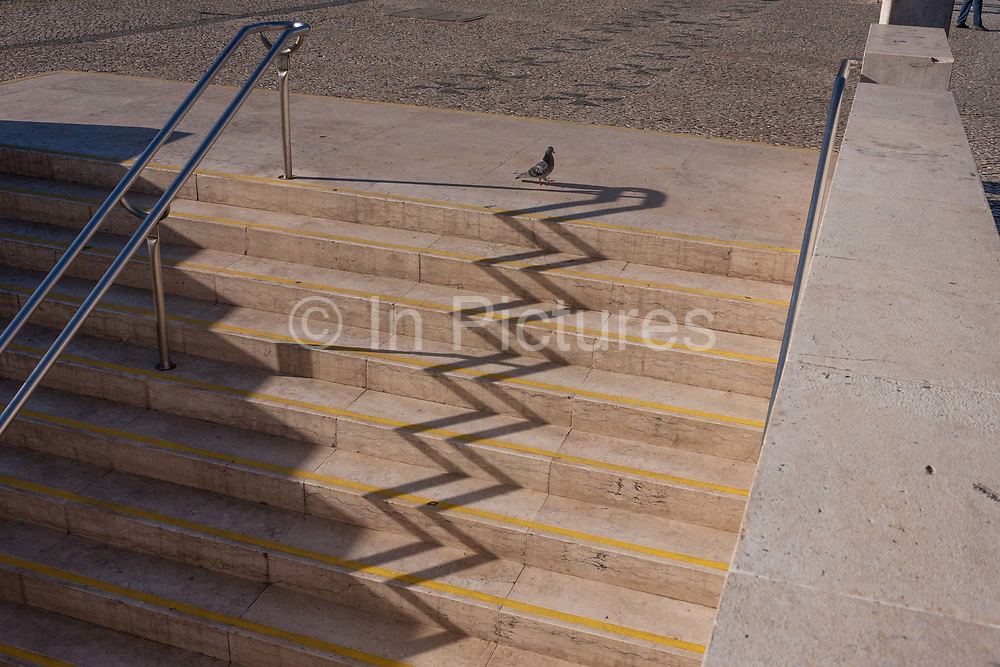 An urban landscape zigzag of shadows from the steps and handrails of Alameda Metro station, on 14th July 2016, in Lisbon, Portugal. One the sunny side are the distorted lines  of the well-trodden stairs at this main transport merge of underground train lines as a lone pigeon walks along the top and persons legs look the same in the far right corner.