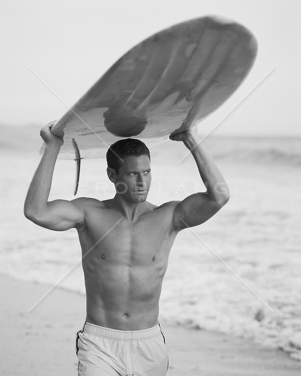 Paul Newman look-a-like surfer carrying his long board on his head walking down the beach
