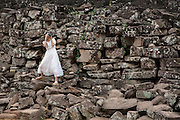 A woman, dressed in a white bridal dress, takes a photo whilst balancing on the ancient stone wall of Angkor Thom, Siem Reap Province, Cambodia, South East Asia. <br /> (photo by Andrew Aitchison / In pictures via Getty Images)