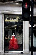 Red wedding dress on a mannequin stands in the window of couture retailer Vera Wang on Brook street, Mayfair, London. From the outside, we see a red pedestrian light echoing the theme of red and the name of the garment's designer at the top of the window. Vera Wang is a well-known contemporary bridal designer.