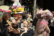 A couple in elaborate hats, with their dogs, which wear equally elaborate hats.