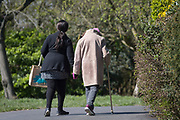 As the UK government considers further restrictions of movement in public places during the Coronavirus pandemic, and the elderly and vulnerable are being given preferential access to supermarkets and shops, a lady walks an elderly person through Brockwell Park in Herne Hill, on 23rd March 2020, in London, England.