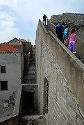 Woman and two children climbing steps on top of walls of Dubrovnik old town, Croatia