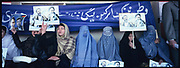 Women hold the pickets of Karim Khalili, left, and Ismail Khan, the warlords of Afghanistan-turned-politicians during a warlords rally in Kabul Stadium.