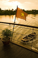 The Vietnamese flag, flapping proudly on a boat on the Mekong Delta at sunset.