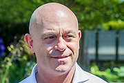 Actor Ross Kemp, on the Hope on the Horizon garden.  The<br /> 'Hope on the Horizon' garden in aid of Help for Heroes: produced by building and landscaping firm Farr and Roberts', making their debut; designed by Matthew Keightley (29), as a result of his brother Michael's involvement with the armed forces, having served on four tours to Afghanistan and due for his fifth this year; and sponsored by the David Brownlow charitable foundation. The garden layout is based on the shape of the Military Cross, the medal awarded for extreme bravery. Granite blocks will represent the soldiers' physical wellbeing and the planting represents their psychological wellbeing at various stages of their rehabilitation. Both evolve through the garden from a rough, unfinished, over-grown beginning through to a perfectly sawn, structured end. An avenue of hornbeams draws the attention through the entire garden to a sculpture resembling a hopeful horizon; a reminder to the soldiers that they all have a bright future ahead. As well as areas to recline and reflect, the garden offers focal points all the way through. Cool, calming colours are used throughout, helping to emphasise the fact that it will be a serene, contemplative space. After the Show, the garden will be moved and set within the grounds at Help for Heroes Recovery Centre at Chavasse VC House in Colchester, Essex. The garden will offer a serene, peaceful haven to contemplate and inspire a bright future and to support the challenging journey to recovery. The Chelsea Flower Show 2014. The Royal Hospital, Chelsea, London, UK.  19 May 2014.