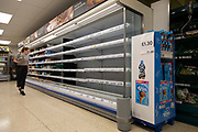 A shopper stands by empty shelves with no stock on them in a Tesco on 22nd July, 2021 in Leeds, United Kingdom. Several supermarkets in the UK have closed branches temporarily as tens of thousands of staff self isolate after being notified by the British NHS app of close Covid-19 contact, impacting staff and supply chains across the nation in what headlines are calling the pingdemic.