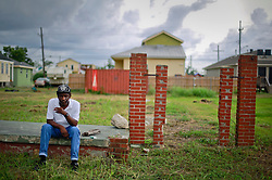 29 August 2014. Lower 9th Ward, New Orleans, Louisiana.<br /> Hurricane Katrina memorial 9 years later. <br /> A Katrina survivor takes a seat amidst the remains of a home on the 9th anniversary of the storm that devastated the region.<br /> Photo; Charlie Varley/varleypix.com