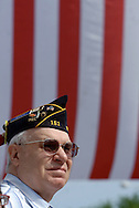 Middletown, NY - A veteran watches the a Memorial Day parade in front of a large American Flag on May 25, 2009.