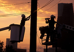Stock photo of a silhouette of two men working on a power pole at sunset