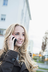 Teenage girl talking on smart phone in city street, Munich, Bavaria, Germany
