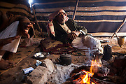 Bedouin men relax by a fire in their remote home encampment in Wadi Rum, Jordan.