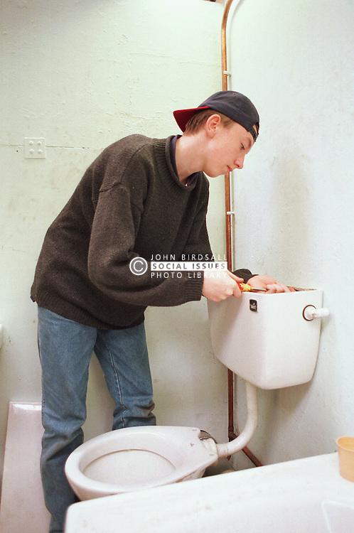 Young man learning plumbing skills mending toilet,