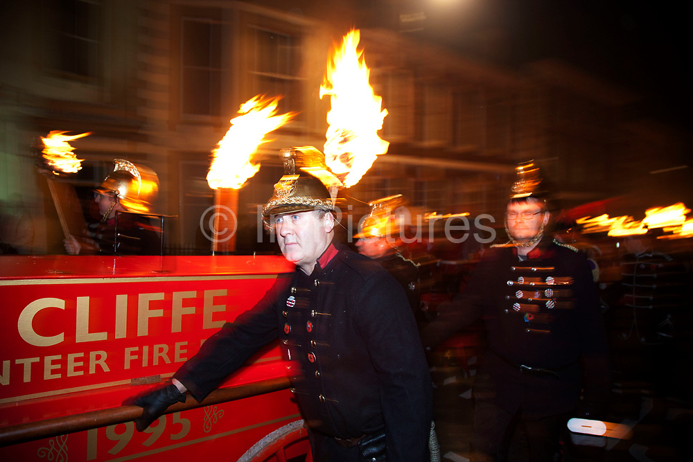 Lewes, UK. Monday 5th November 2012. Cliffe bonfire society members carry burning torches as Cliffe Volunteer Fire Service. Bonfire Night celebration in the town of Lewes, East Sussex, UK which form the largest and most famous Guy Fawkes Night festivities. Held on 5 November, the event not only marks the date of the uncovering of the Gunpowder Treason and Plot in 1605, but also commemorates the memory of the 17 Protestant martyrs from the town burnt at the stake for their faith during the Marian Persecutions of 1555–57. There are six bonfire societies putting on parades involving some 3,000 people.