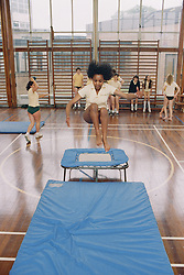 Secondary school girl jumping off trampoline in sports hall during physical exercise class,