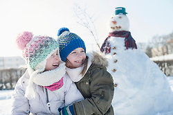 Girls embracing against snowman