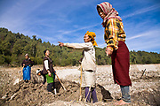 A group of Apatani tribal women re-contour the bare rice fields after having been harvested. Most villagers own small plots of land which are mainly used for rice growing and usually  friends and neighbours help one another plough and till the land for the coming growing season. Hijja Village, Arunachal Pradesh, India.