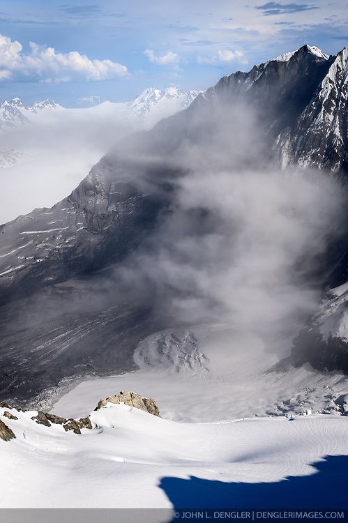 """A 4,000-foot-high mountainside released approximately 120 million metric tons of rock in 60 seconds during a landslide onto the Lamplugh Glacier in Glacier Bay National Park and Preserve. In an interview with the Alaska Dispatch News, geophysicist Colin Stark of Columbia University's Lamont-Doherty Earth Observatory, described the slide as """"exceptionally large."""" He compared the massive landslide to roughly 60 million medium SUVs tumbling down a mountainside.<br /> <br /> Mountainsides that were held strong by the heavy ice of glaciers become weak when the glaciers retreat. Erosion along with earthquakes are triggers that can cause the weakened slopes to collapse.<br /> <br /> The slide occurred on the morning of June 28  in a remote area of Glacier Bay National Park in southeast Alaska. It was first observed by Paul Swanstrom, pilot and owner of Haines-based Mountain Flying Service. Swanstrom noticed a huge cloud of dust over the Lamplugh Glacier during a flightseeing tour of Glacier Bay National Park several hours after the slide occurred. Swanstrom estimates the debris field to be 6.5 miles long, and one to two miles in width.<br /> <br /> Even two days later, as this aerial photo of the Lamplugh Glacier landslide shows, a dust cloud remained over the unstable mountainside due to still tumbling rock."""