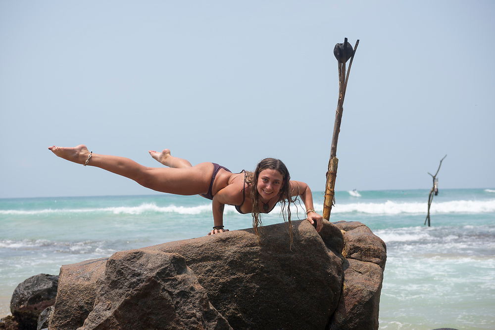 A young woman on vacation in Mirissa, Sri Lanka, balances her body weight using only her arms on a boulder at the beach