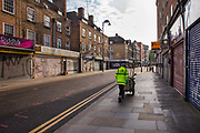 Street cleaner on closed Petticoat Lane market overlooked by City of London skyline during the coronavirus pandemic on the 4th May 2020 in London, United Kingdom.