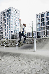 Young woman walking on net in playground, Munich, Bavaria, Germany