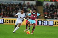 Alex Song of West Ham Utd ® is challenged by Andre Ayew of Swansea city (l).Barclays Premier league match, Swansea city v West Ham Utd at the Liberty Stadium in Swansea, South Wales  on Sunday 20th December 2015.<br /> pic by  Andrew Orchard, Andrew Orchard sports photography.