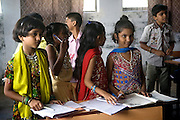 Children are following a lesson at a school run by Sonrisas de Bombay, a fast-growing Spanish NGO in Mumbai, India.