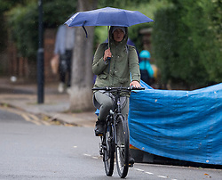 © Licensed to London News Pictures. 13/06/2021. London, UK. A cyclists shelters underneath an umbrella form the rain while making her way through Queens Park in north west London at rush hour, on another grey and damp summer's day. Photo credit: Ben Cawthra/LNP