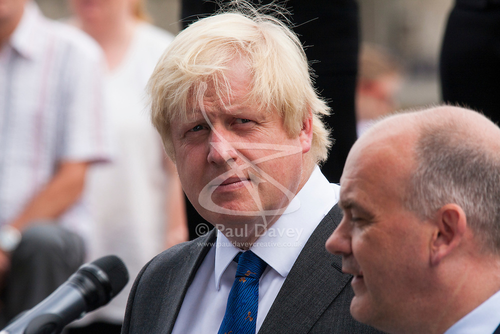 London, June 23rd 2014. Mayor of London Boris Johnson listens as Roger Evans, Chairman of the London Assembly addresses members and veterans of the armed forces as they gather at City Hall for a flag raising ceremony to mark Armed Forces Day