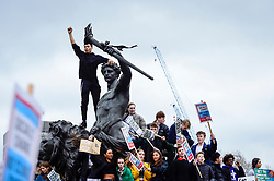 © Licensed to London News Pictures. 15/03/2019. LONDON, UK. Students climb the statues on the Queen Victoria Memorial by Buckingham Palace. Thousands of students take part in a Climate Change strike in Parliament Square, marching down Whitehall to Buckingham Palace.  Similar strikes by students are taking part around the world demanding that governments take action against the effects of climate change.  Photo credit: Stephen Chung/LNP