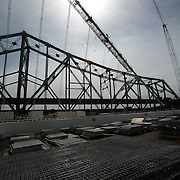 The San Francisco-Oakland Bay Bridge is under construction, and scheduled to open Labor Day 2013. The Self-Anchored Suspension Span (SAS) is the largest bridge of its kind in the world measuring 2,047 feet. This engineering and construction marvel raises the bridge building bar to new heights, as seen in these behind the scenes photos taken on Monday, March 18, 2013. This images shows the new span, with the original 2 story bridge section in the background. (AP Photo/Alex Menendez)