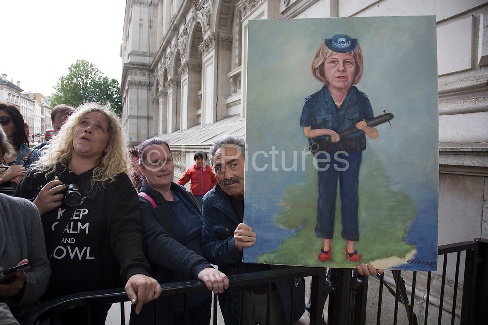 Political artist Kaya Mar with his latest painting on the day that the new Conservative Party leader Theresa May MP became Prime Minister of the UK, as protesters and public gathered outside Downing Street on 13th July 2016 in London, United Kingdom. This painting portrays Theresa May as a thuggish police woman holding a truncheon with a nail through it. Political satire on her hardline dealings with the police force. photo by /In Pictures via Getty Images