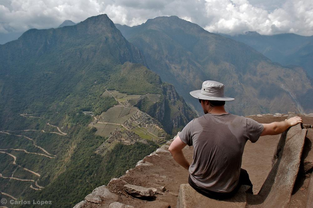 A tourist is admiring the lost Inca city of Machu Picchu, located in Cusco, Peru