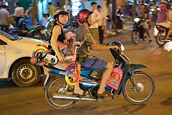 Family On Motorbike Holding Bicycle