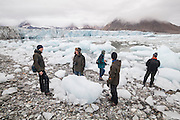 Men explore the calved icebergs filling the forebay of Hansbreen, Hornsund, Svalbard.