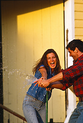 couple outdoors playing with a garden hose