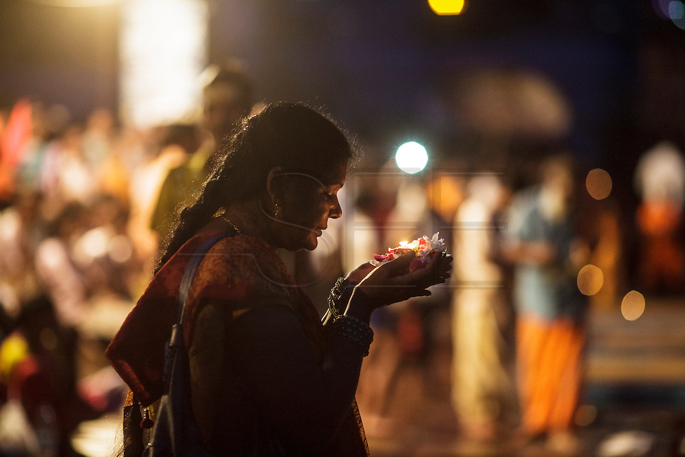 Women praying before sending an offering to the river at Dashashwamedh Gath by the Ganges River in Varanasi, India.