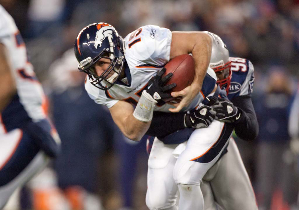 Foxborough, MA 01/14/2012.Broncos quarterback Tim Tebow is sacked by Patriots defensive lineman Gerard Warren in the first half of Saturday's AFC Divisional game between the New England Patriots and the Denver Broncos..Wicked Local Photo by Alex Jones