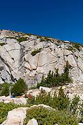 Two teenage boys climb the rocks above Selden Pass. John Muir Wilderness, Sierra National Forest, Sierra Nevada Mountains, California, USA.