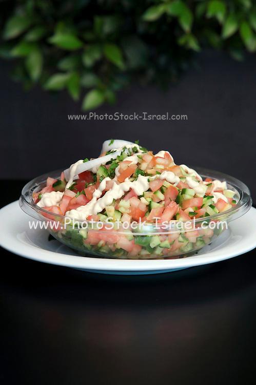 Fresh salad of diced tomato, cucumber, herbs, lemon juice and tahini sauce