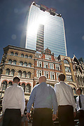 "London, UK. Thursday 5th September 2013. City workers looking up into the light. Urgent action in planned to ""cover up"" the Walkie Talkie skyscraper in the City after sunlight reflected from the building melted a car on the streets below. Temperatures have been measured in excess of 50 degrees C, and as much as 70 degrees at it's peak. The 525ft building has been renamed the ""Walkie Scorchie"" after its distinctive concave surfaces reflected a dazzling beam of light which has caused extensive damage to nearby buildings."