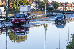 Licensed to London News Pictures. 05/10/2021. London, UK. Car car passes an abandon car stuck in flood water on the A3 Kingston Bypass, South West London this morning. The A3 a main route in and out of London was closed this morning after torrential rain caused flooding on the carriage way as traffic built up on surrounding roads. Torrential rain last night has caused severe flooding in London with many roads blocked with flood water and broken down cars. Photo credit: Alex Lentati/LNP