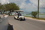 People in a battery run golf cart, the local alternative to cars on Harbour Island, The Bahamas